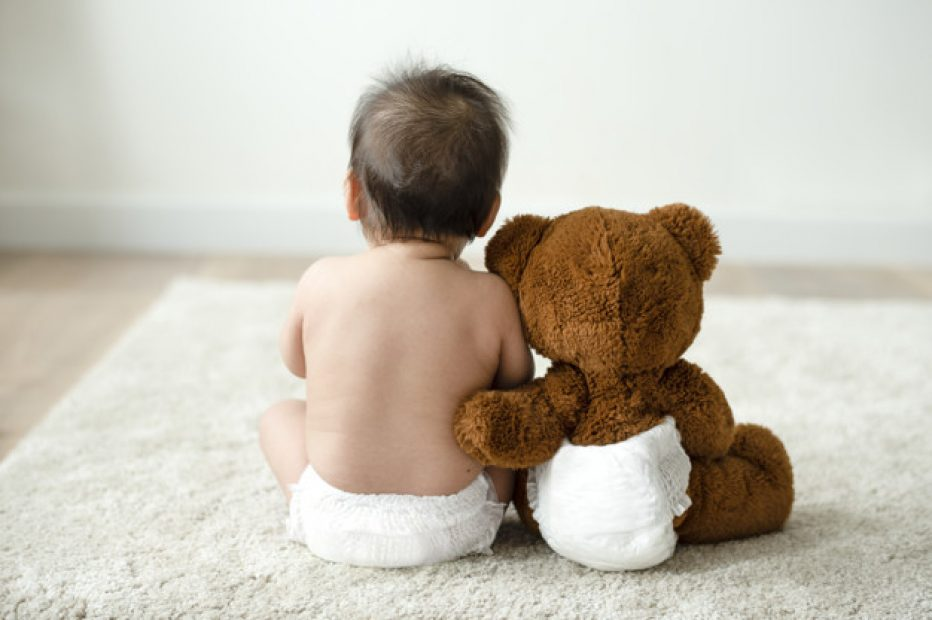 Back of a baby with a teddy bear